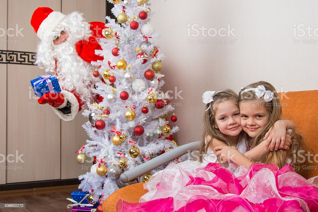 Two girls hug on the couch, santa claus peeping from stock photo