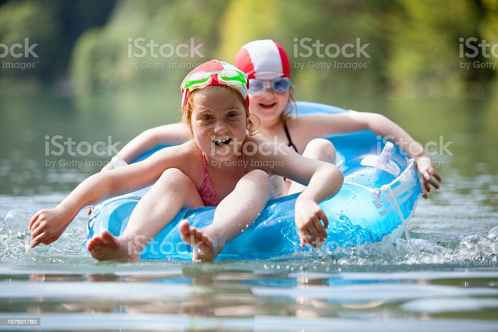 Two girls in a rubber dinghy stock photo