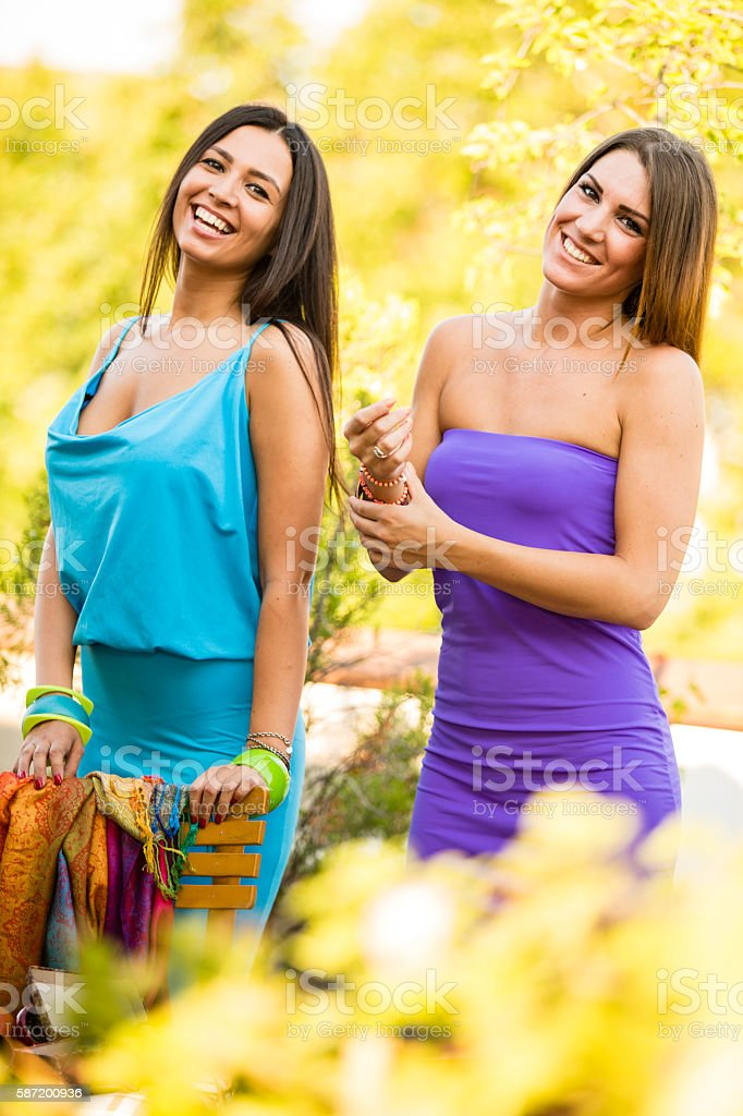 Two girls in colorful dresses outdoors stock photo