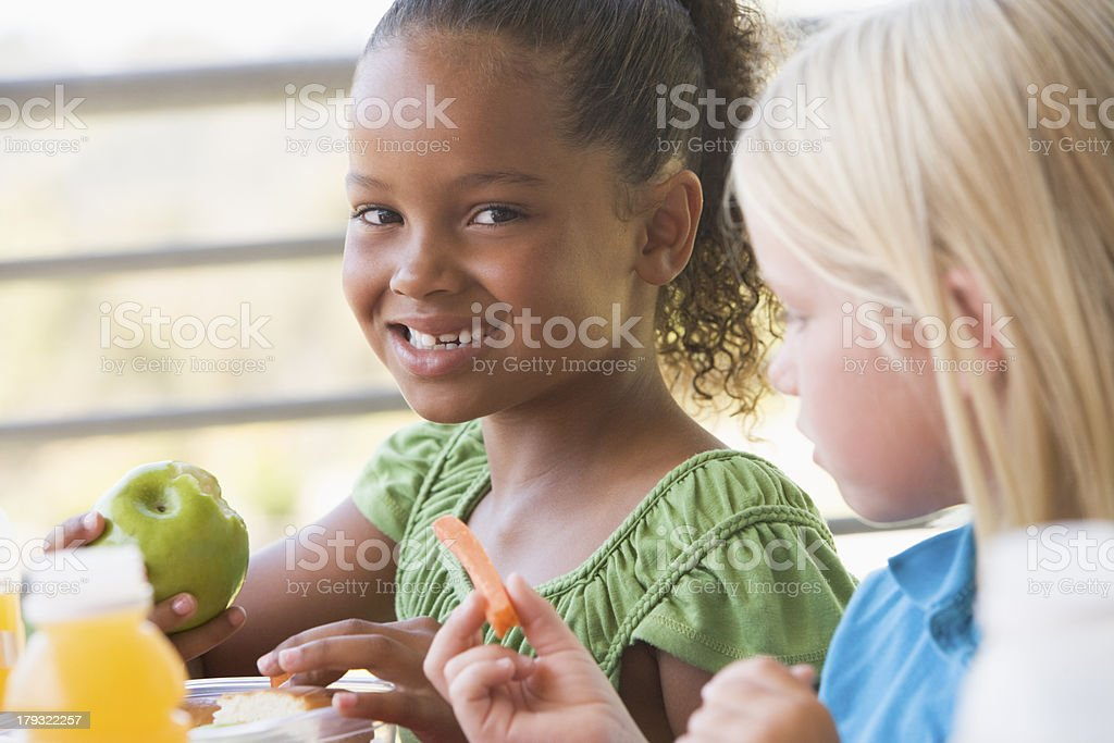 Two girls in kindergarten eating lunch stock photo