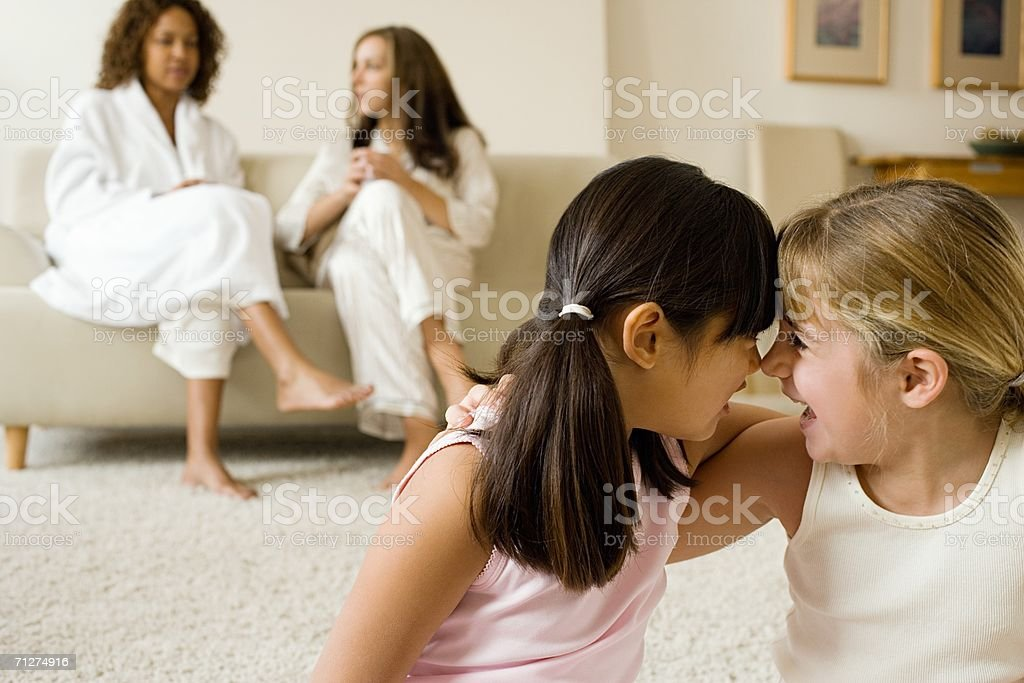 Two girls in living room hugging royalty-free stock photo