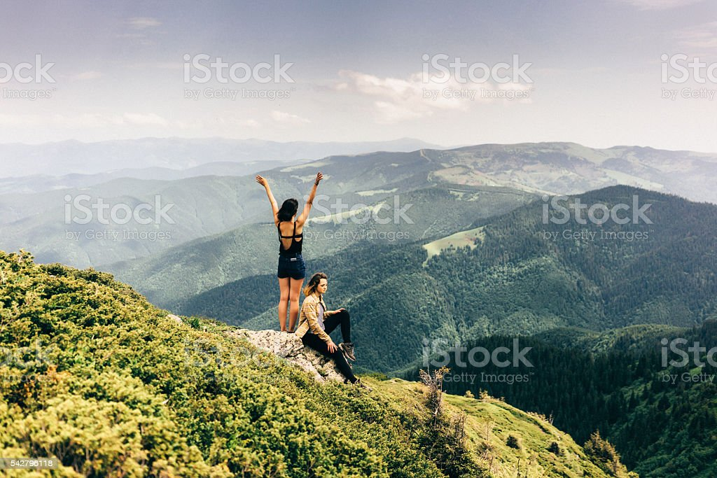 Two girls in mountains stock photo