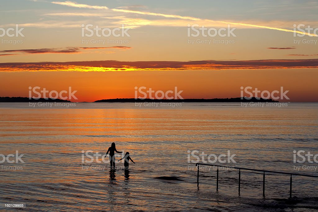 Two girls in sea with sunset royalty-free stock photo