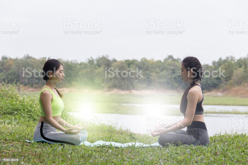 Two Girls in sportware doing pose yoga on river side stock photo