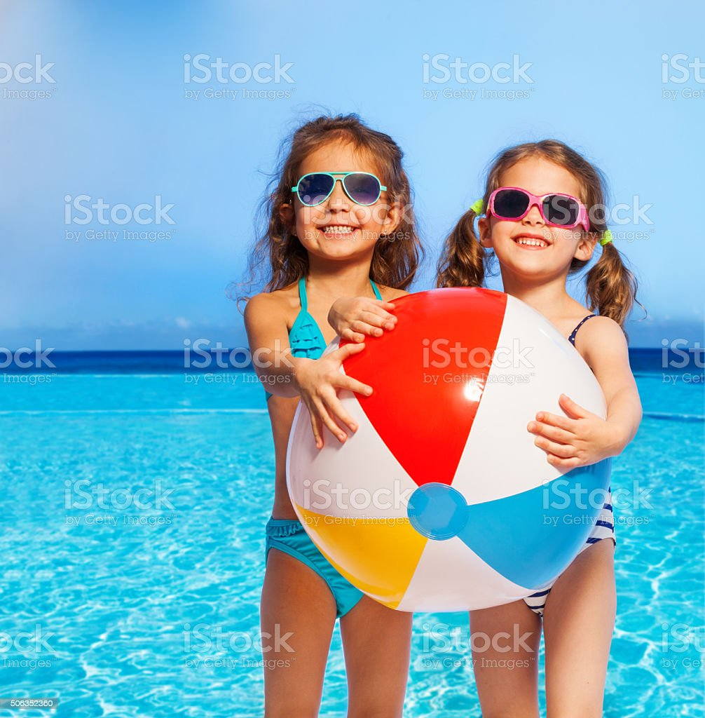 Two girls in swimwear with big inflatable ball stock photo