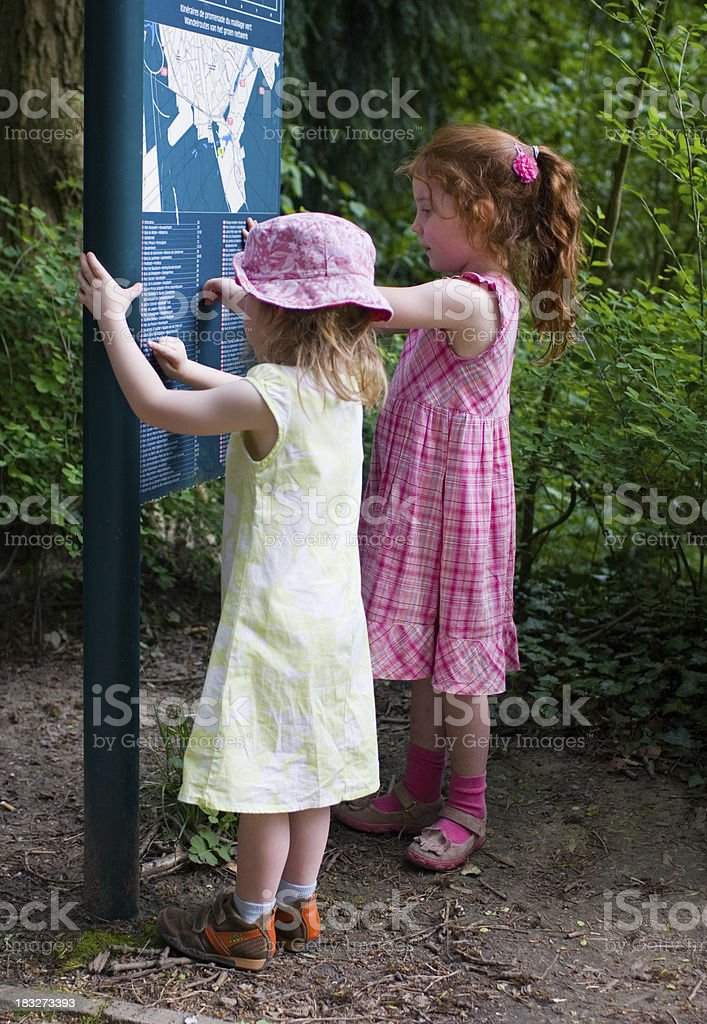 Two girls in the forest, reading a map sign royalty-free stock photo