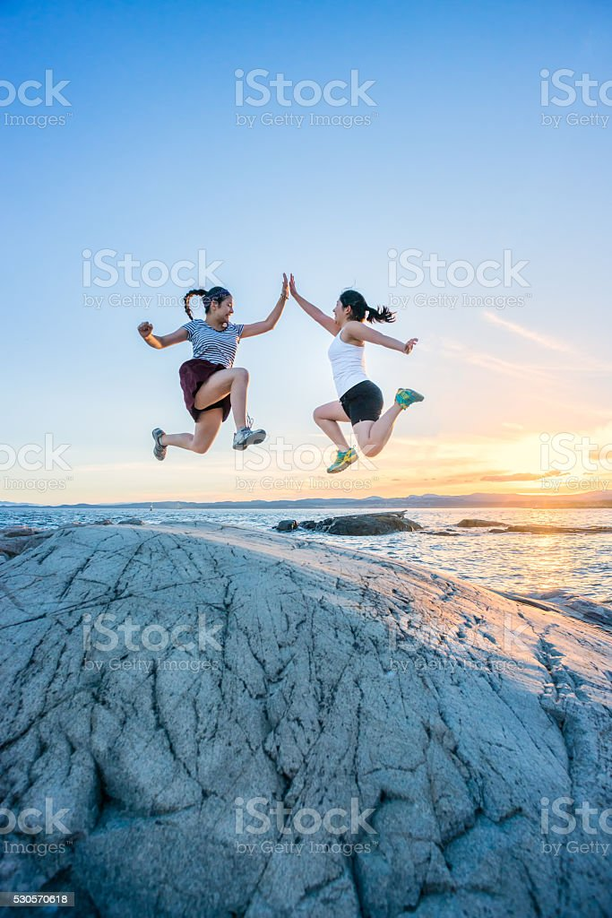 Two Girls Jumping and Giving High Fives on Rocky Beach stock photo