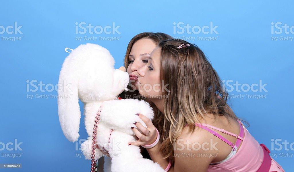 Two girls kissing a plush rabbit royalty-free stock photo
