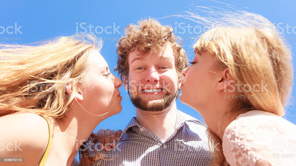 Two girls kissing one boy having fun outdoor stock photo