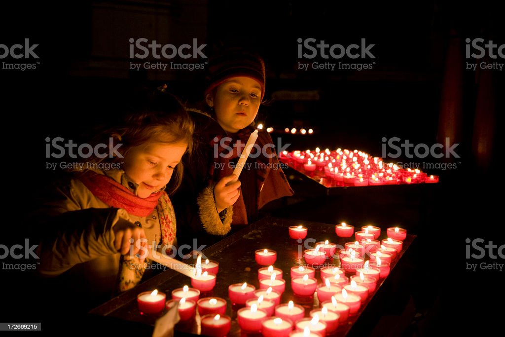 Two girls lighting red candles in church royalty-free stock photo