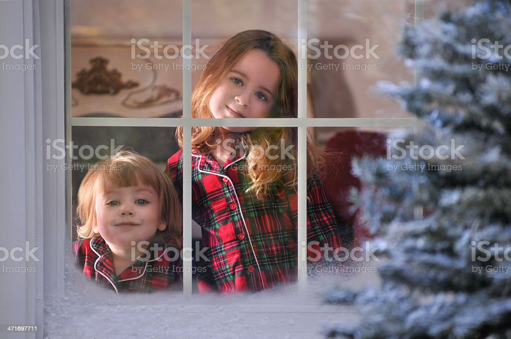 Two Girls Look Outside their Window to a Winter Wonderland royalty-free stock photo
