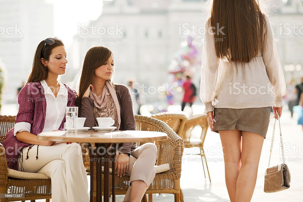 Two girls looking at the girl passing by. stock photo