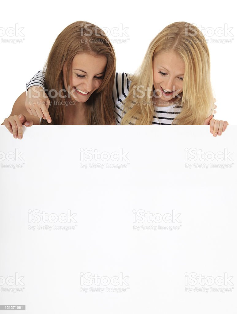 Two girls looking down blank sign stock photo