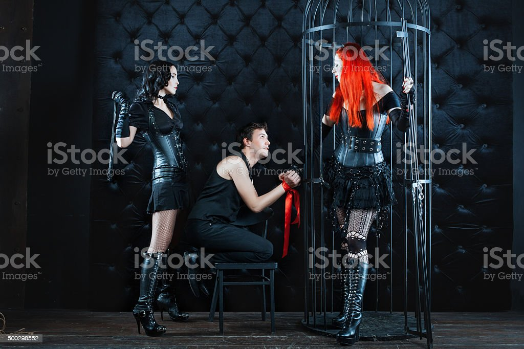 Two girls mistress dominate man. stock photo