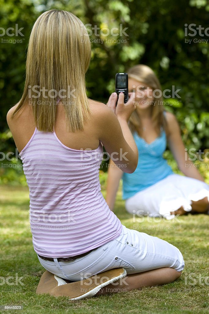 Two Girls Outside Taking PIctures Using A Camera Phone royalty-free stock photo