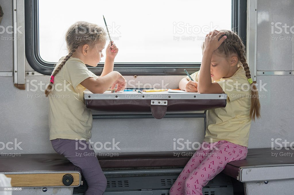 Two girls painted for the side table second-class train carriage stock photo