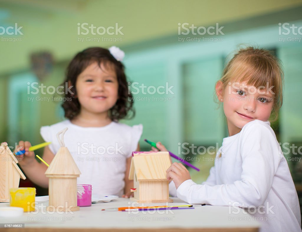 Two girls painting little wooden houses stock photo