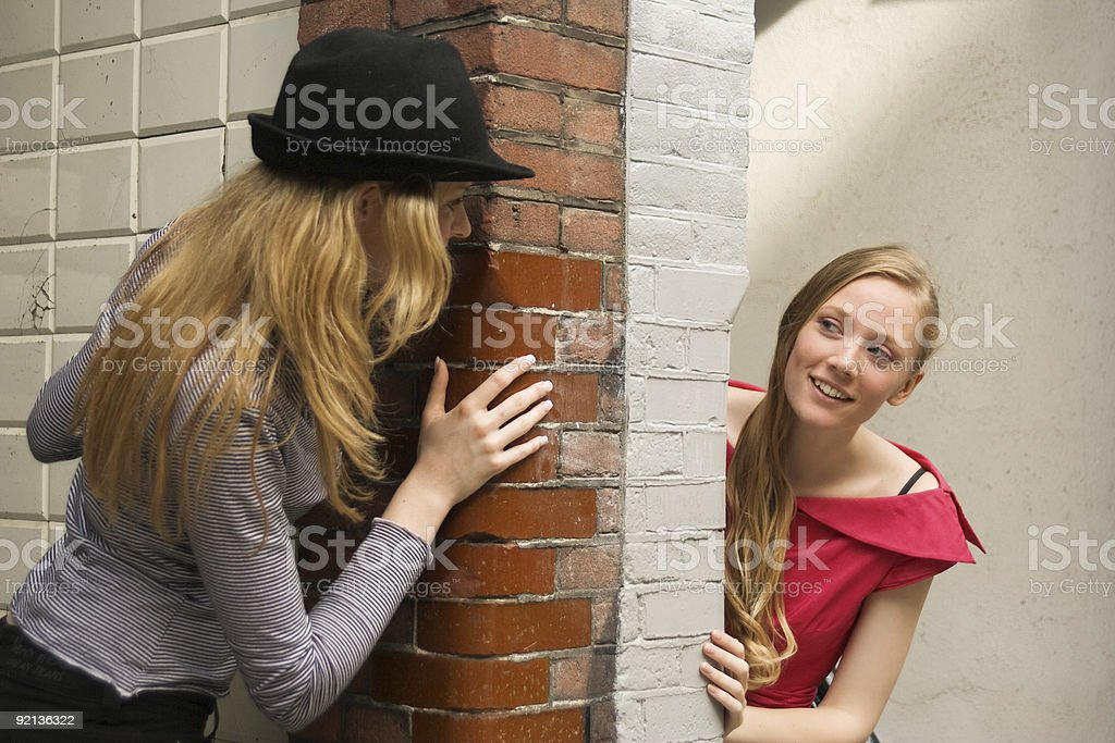 Two girls peeking around the wall royalty-free stock photo