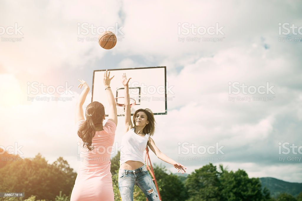Two Girls Playing Basketball on Outdoor Court stock photo