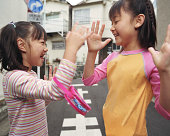 Two girls (6-9) playing clapping game, side view