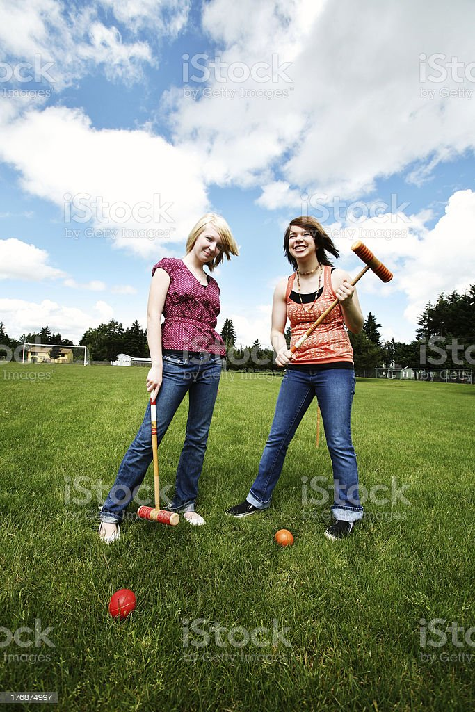 Two Girls Playing Croquet Outside stock photo