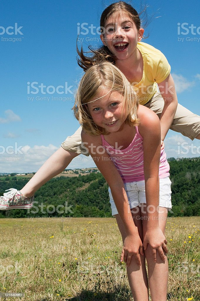 Two girls playing leapfrog in field stock photo