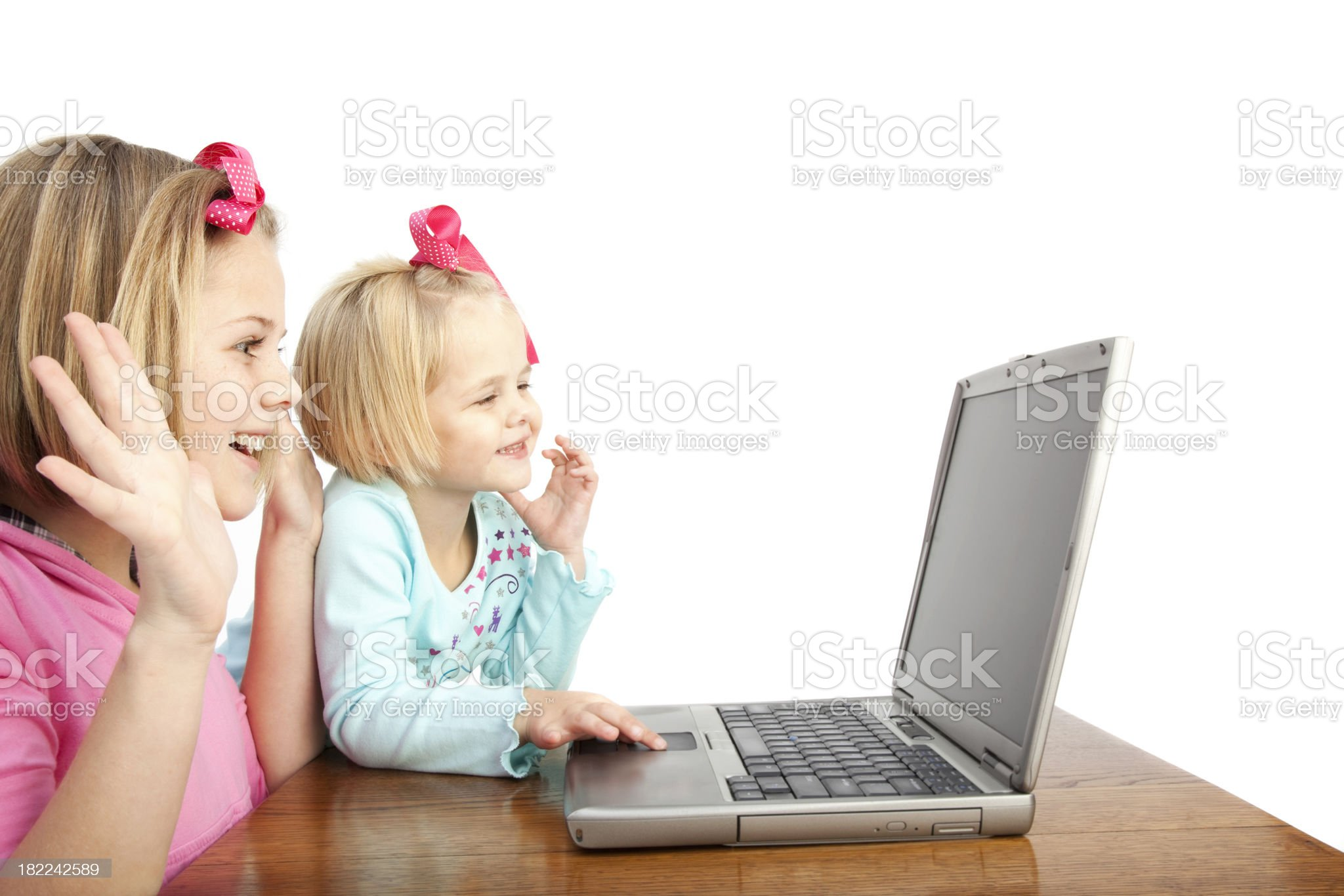 Two girls playing on a laptop computer royalty-free stock photo