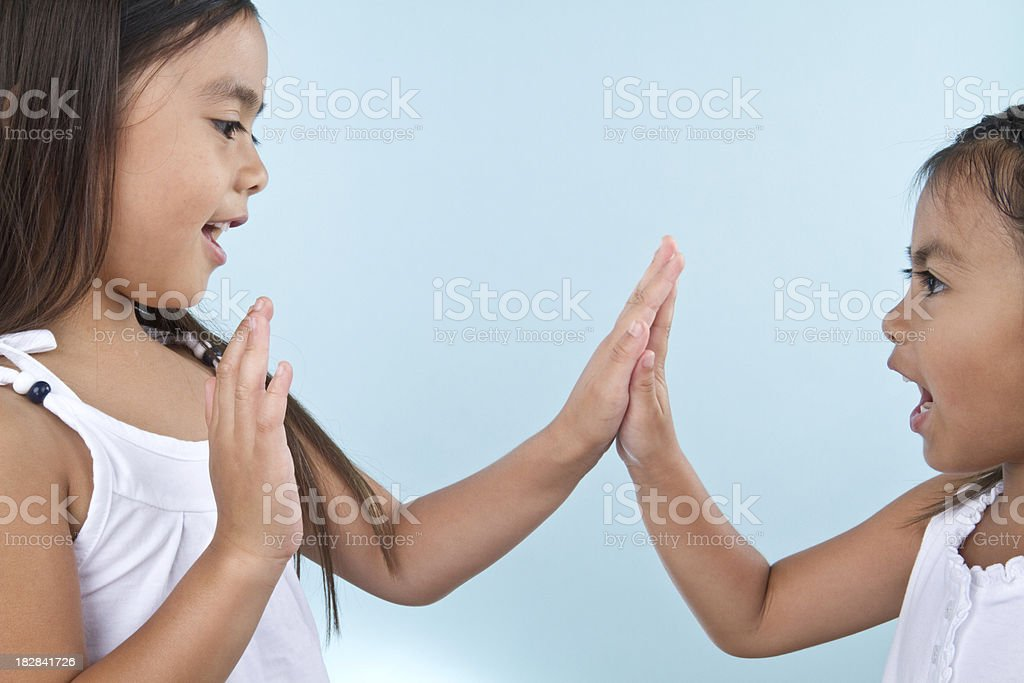two girls playing patty cakes stock photo