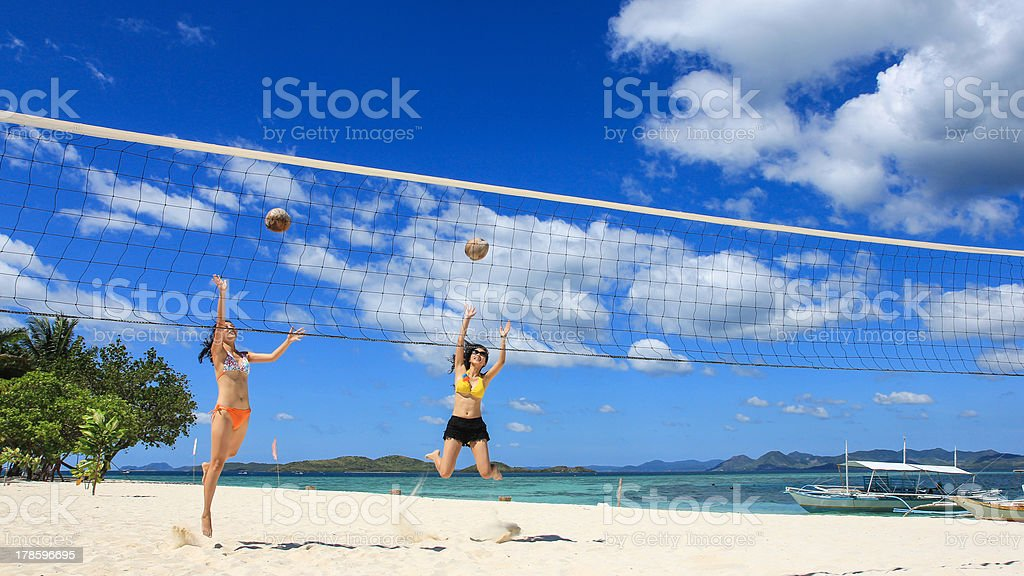two girls playing volleyball on white beach royalty-free stock photo