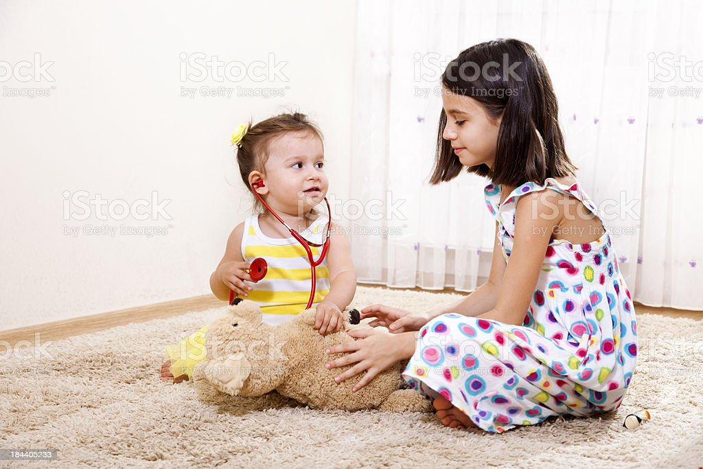 Two girls  playing with bear in living room, smiling royalty-free stock photo