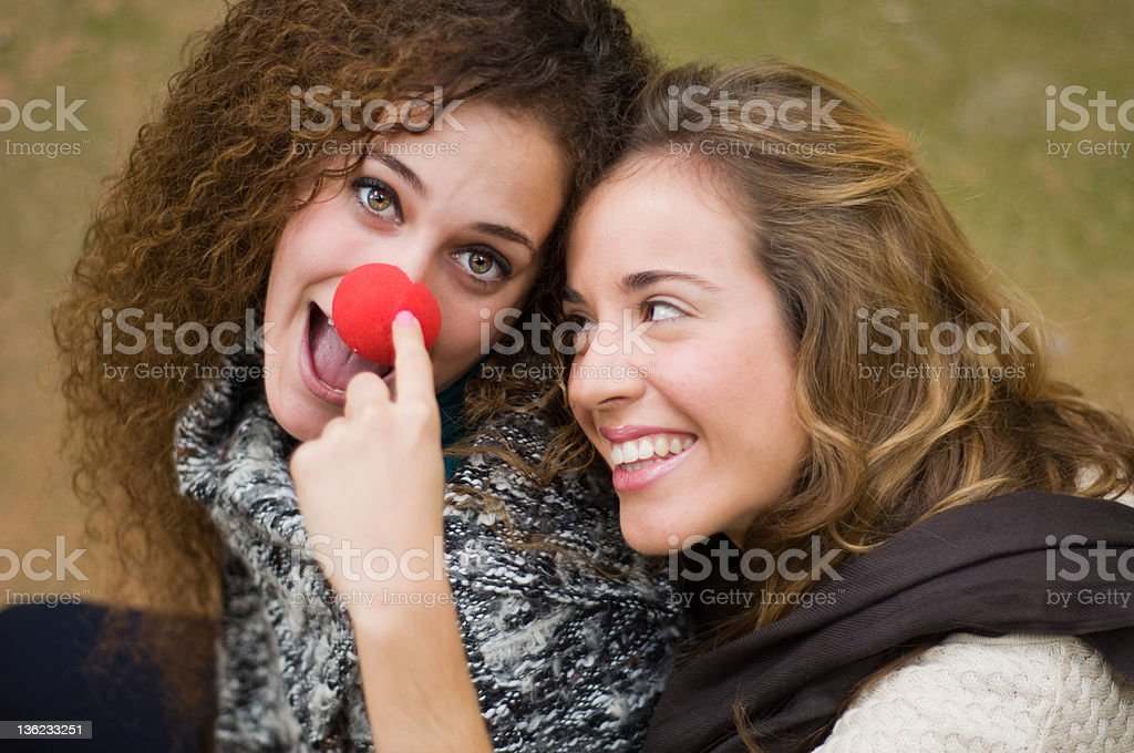 Two girls playing with clown nose stock photo
