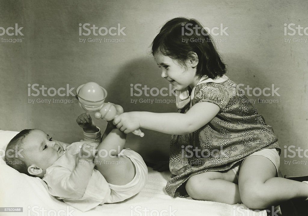 Two girls (6-12 months) (3-4) playing with rattle, (B&W) stock photo