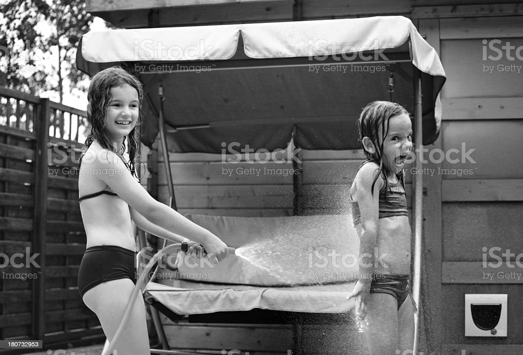 two girls playing with water in garden stock photo