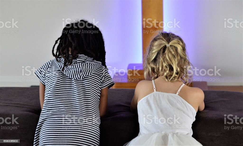 Two girls pray at the foot of the cross stock photo