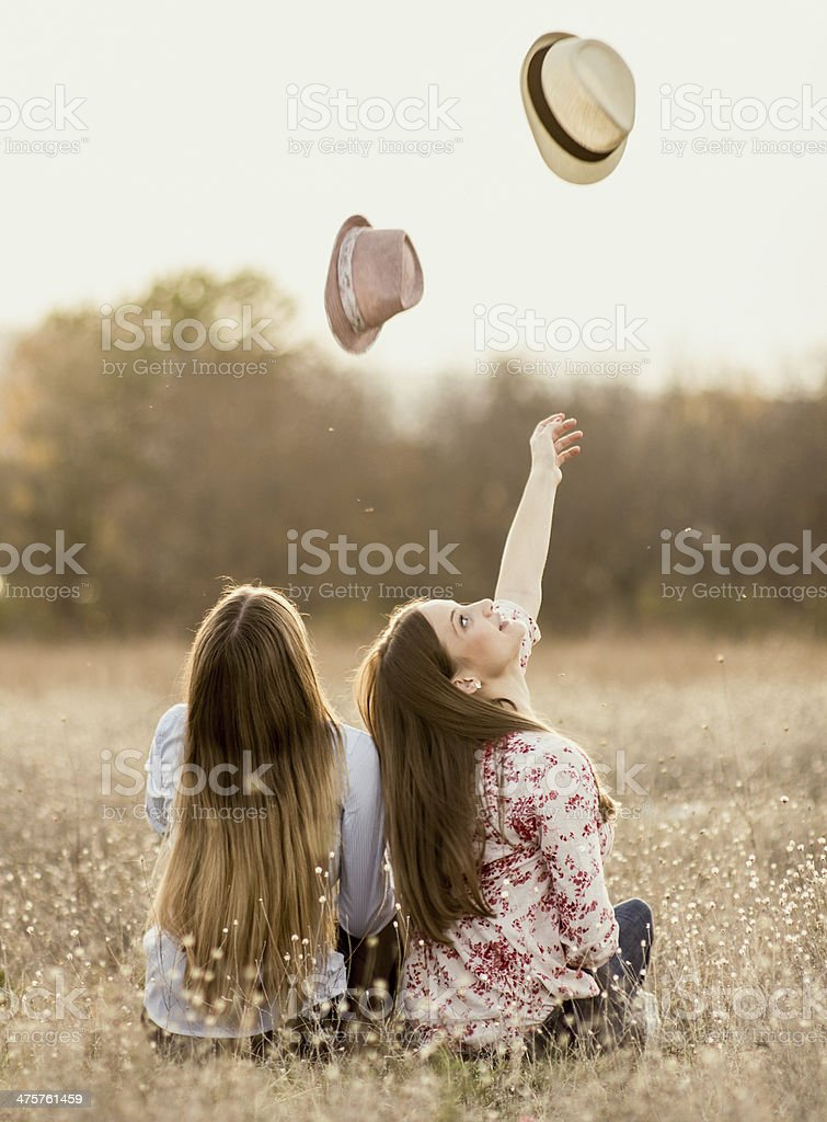 Two girls relax in meadow stock photo