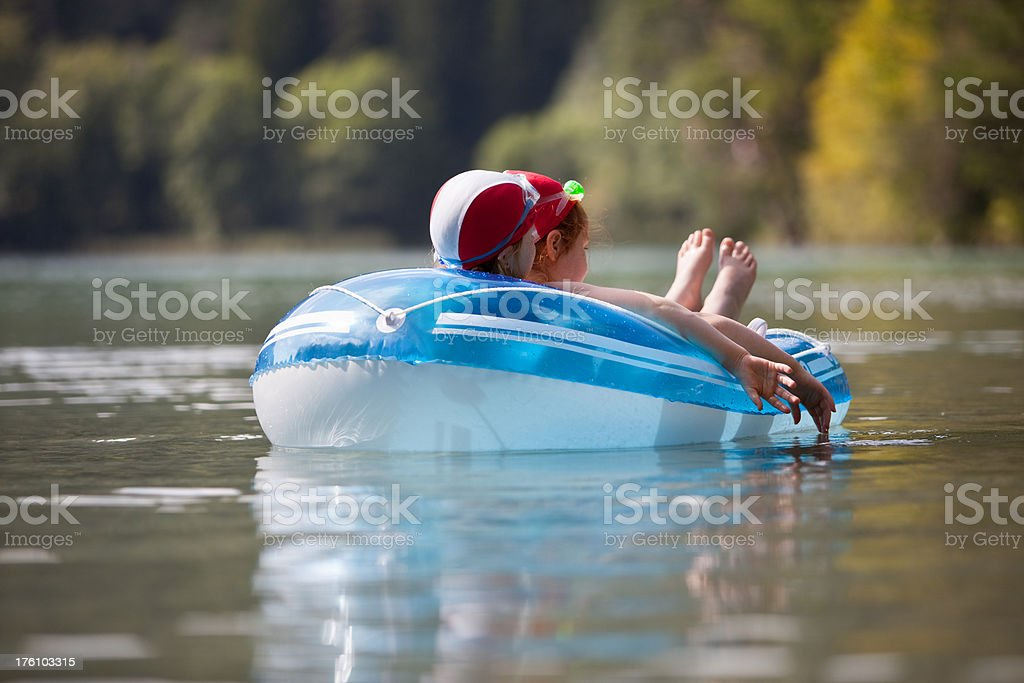Two girls relaxing in a rubber dinghy at the lake stock photo