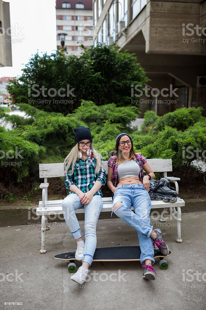 Two girls relaxing on the bench stock photo