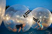 Two girls roll inside giant plastic balls