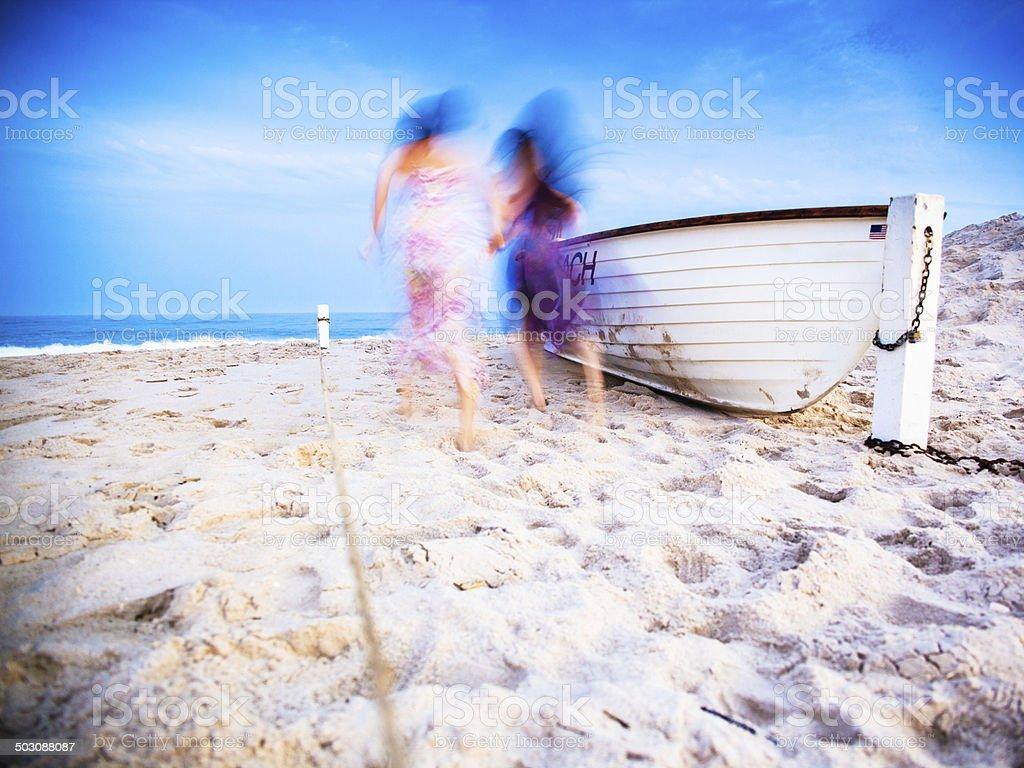 Two girls running at the Jones Beach at the sunset stock photo