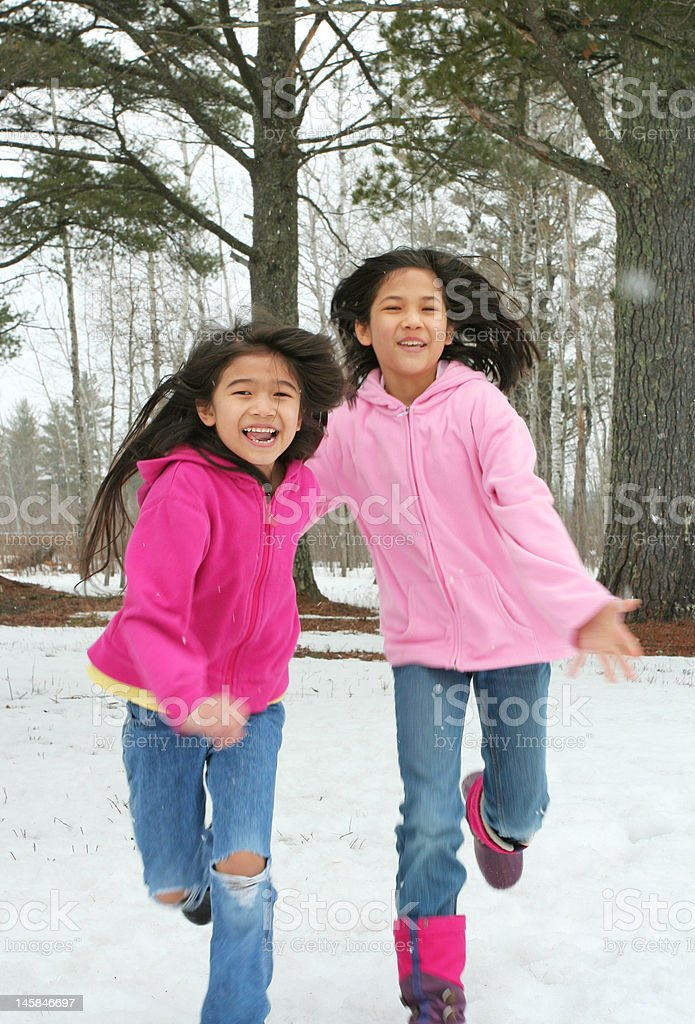 Two girls running through the snow royalty-free stock photo