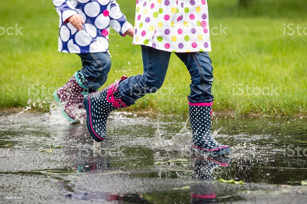 Two Girls Running Through Water Puddle in Rain stock photo
