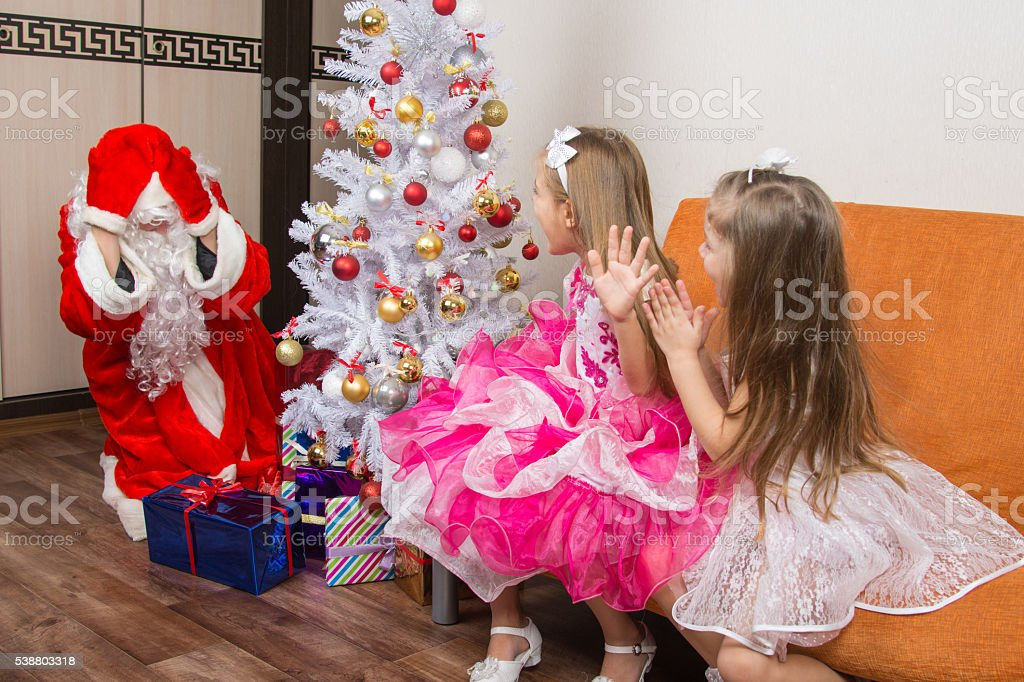 Two girls saw Santa Claus who brought them gifts stock photo