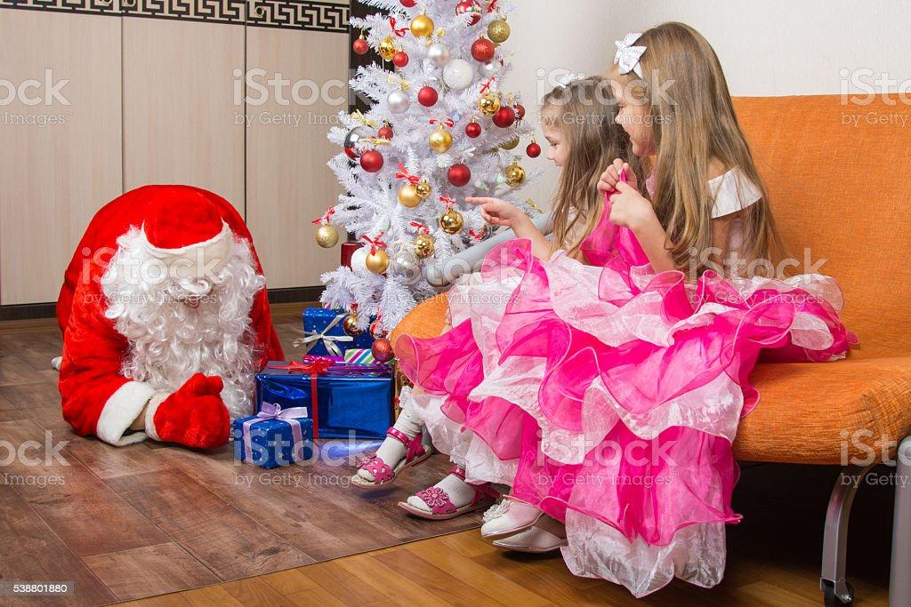 Two girls saw that Santa Claus puts presents stock photo