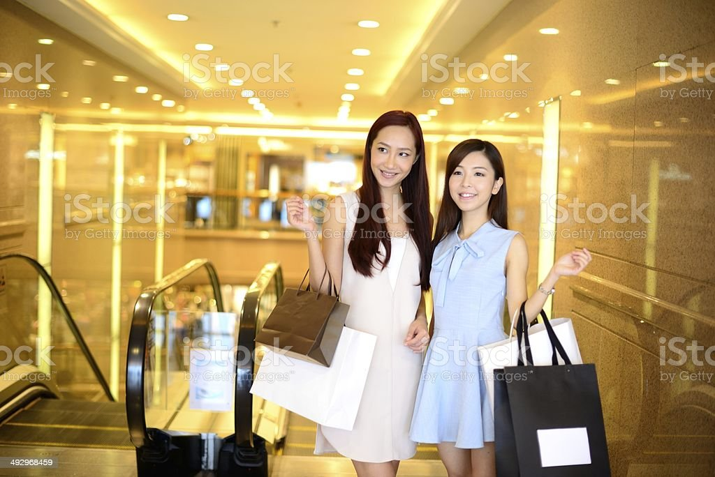 Two girls shopping in a mall stock photo