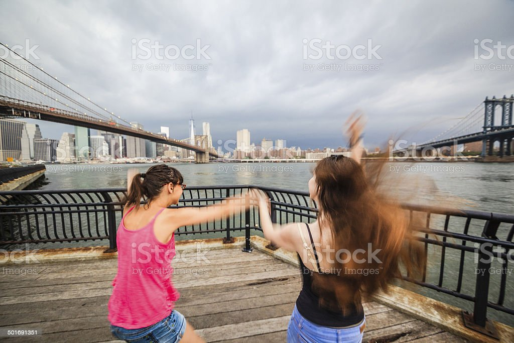 Two girls, sisters, looking to Manhattan under thunderstorm stock photo