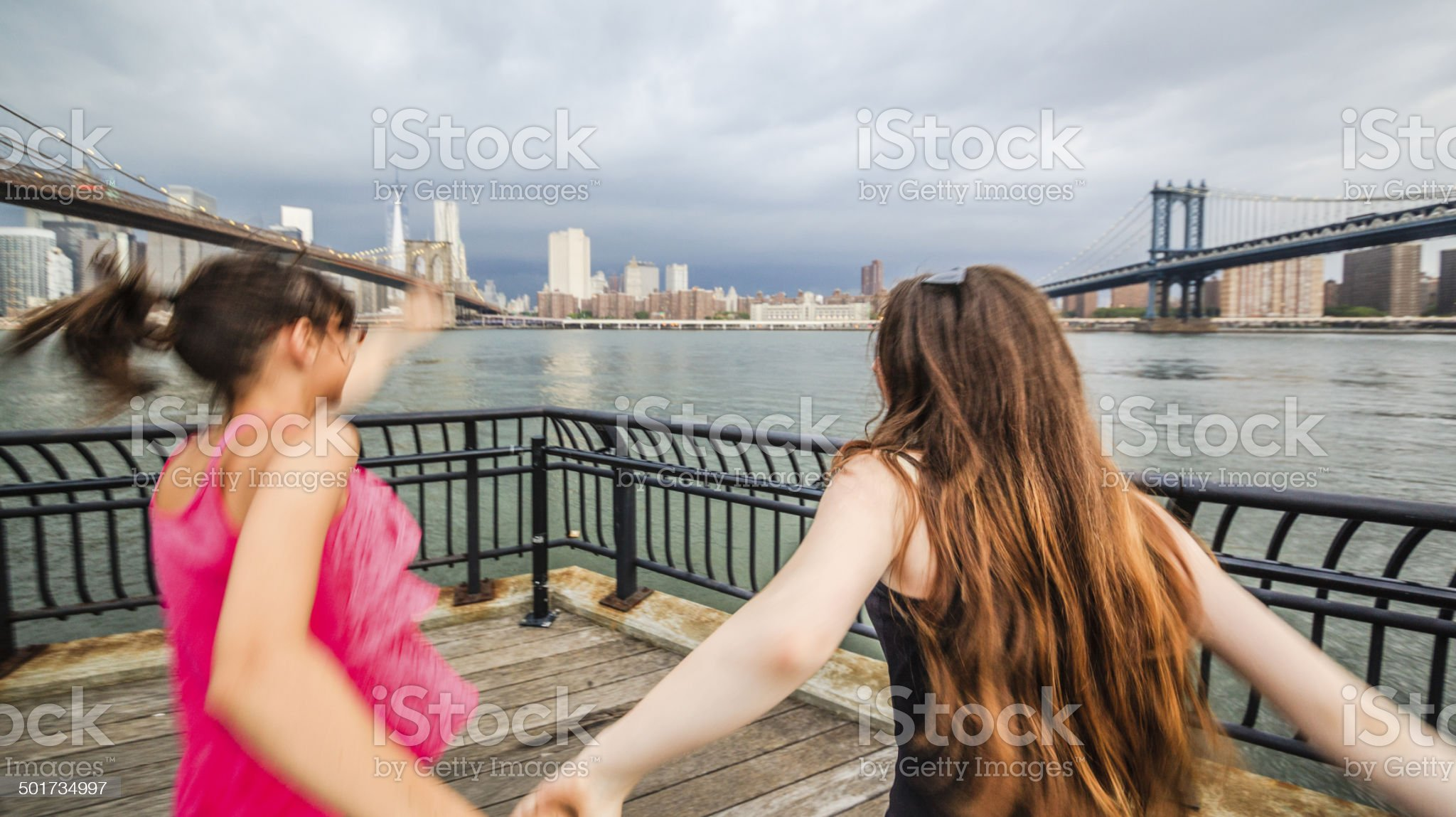 Two girls, sisters, looking to Manhattan under thunderstorm royalty-free stock photo