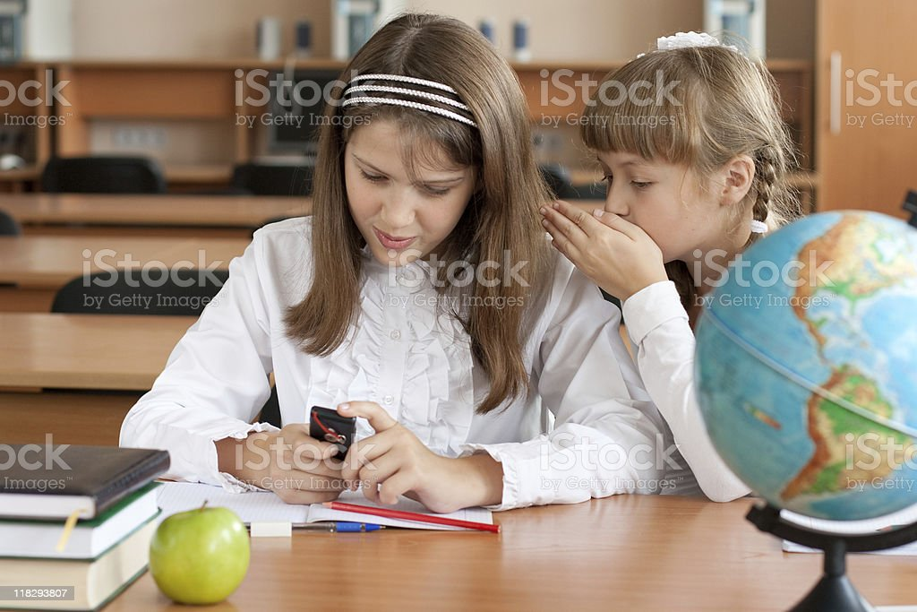 Two girls sitting at school desk with mobile phone royalty-free stock photo