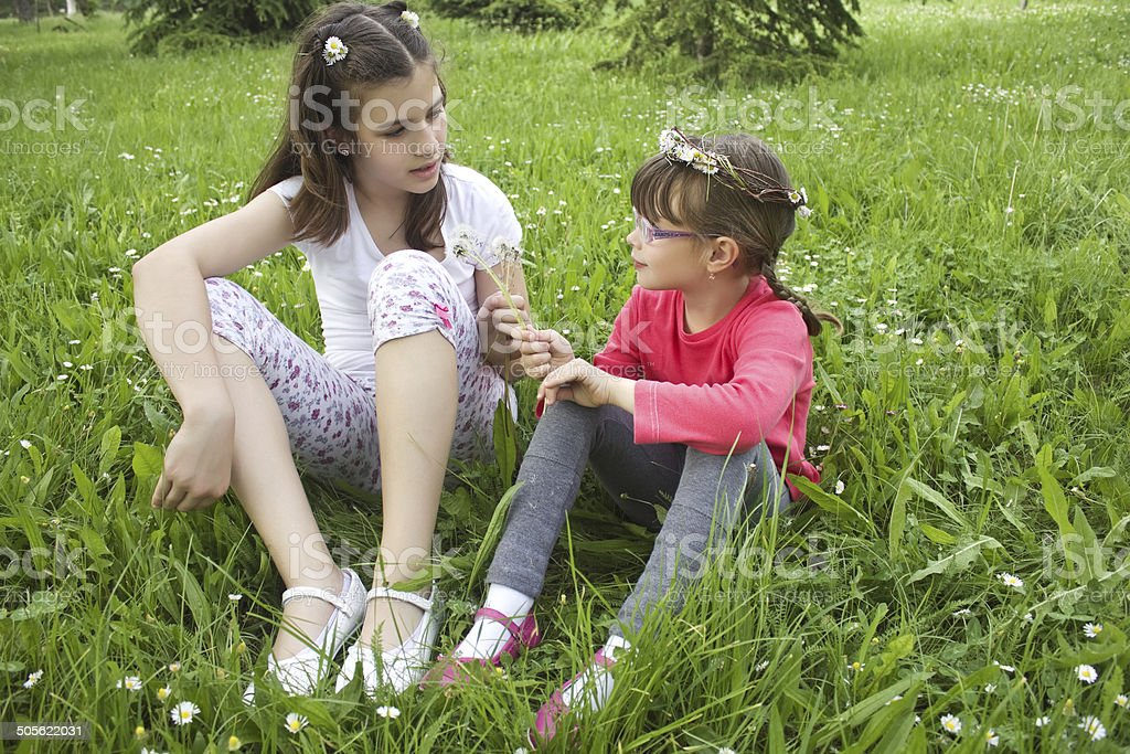 two girls sitting in the grass stock photo