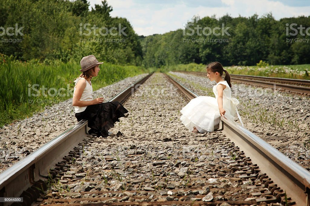 Two girls sitting on a railroad track royalty-free stock photo