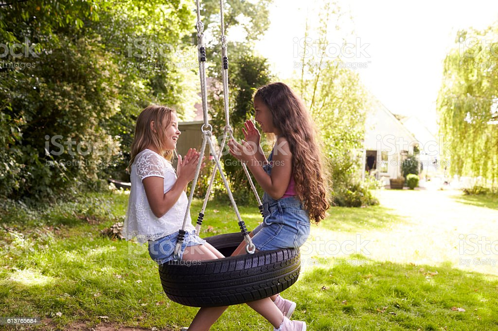 Two Girls Sitting On Swing Playing Clapping Game stock photo